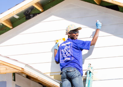 Smiling volunteer standing on a ladder and painting siding on front of house