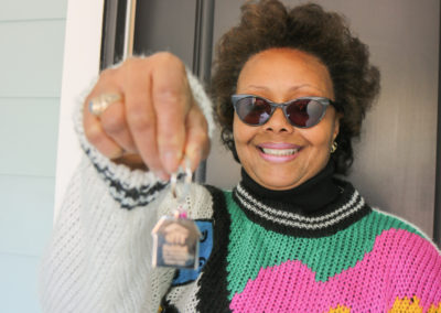 A woman holds out a house keychain in front of a door.