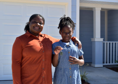 A woman puts her arm around her daughter in front of their new home