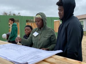 A woman and two young men look at house plans.