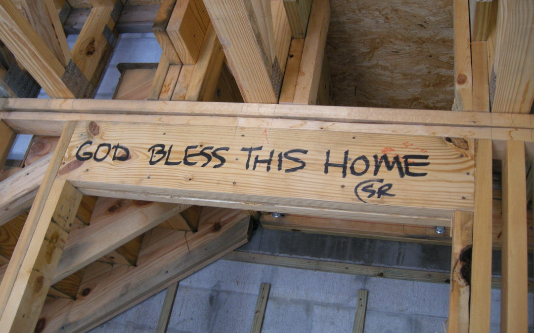 """God Bless This Home"" is written on the boards of a house."