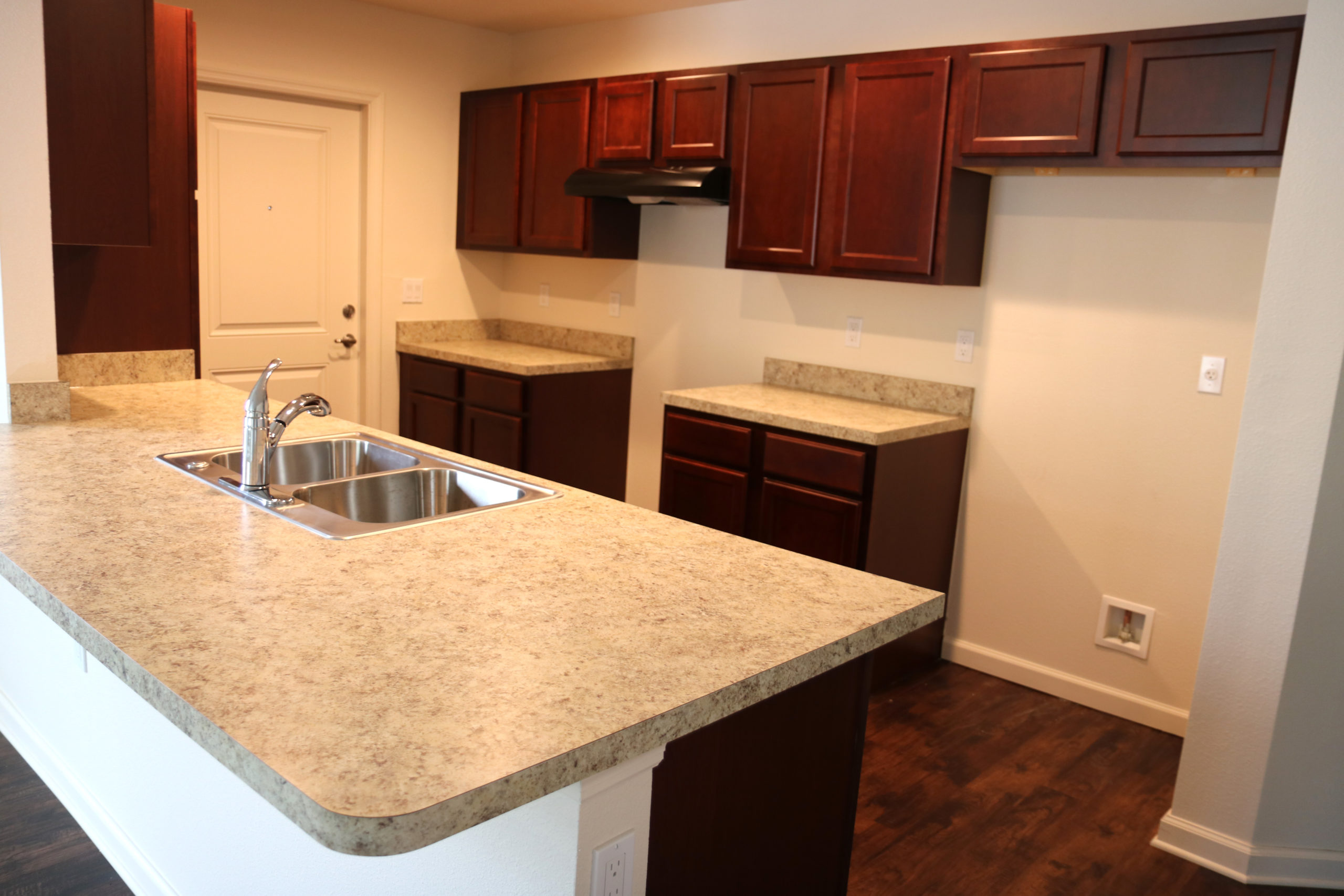 A kitchen with cabernet cabinetry and beige countertops in the Habitat Orlando community of Silver Pines Pointe.