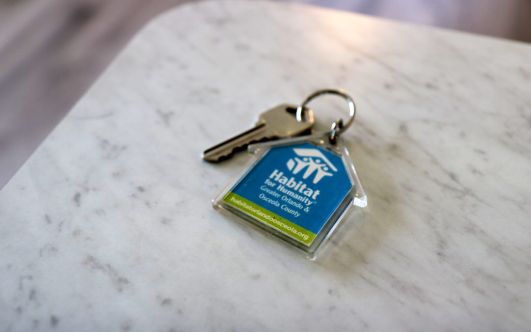 A key on a Habitat keychain sits on a white countertop.