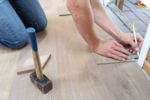 A person takes measurements as he or she lays flooring.