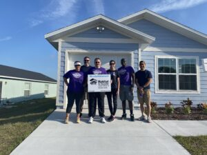 A team from Universal Orlando poses in front of a house with a Habitat sign.