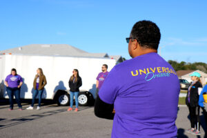 A man in a Universal Orlando shirt stands in a circle awaiting instruction.