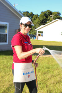 A Bank of America volunteer waters a Habitat home's lawn.