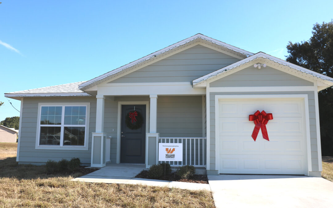 """A Habitat home with a red bow on the garage door and a sign reading """"Williams Company"""" in front."""