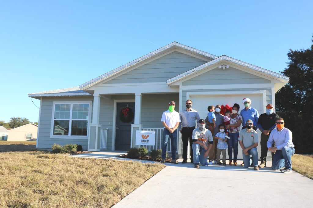The Bogan family, Williams Company representatives and Habitat staff members pose in front of a Habitat home.
