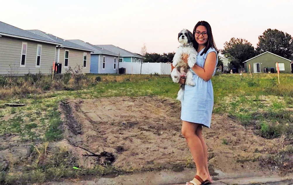 woman stands with her dog at dirt lot where her home will be built