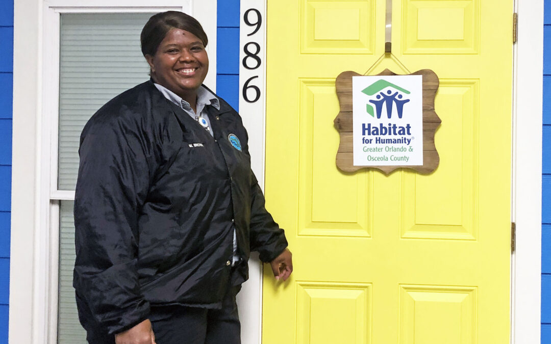 Smiling woman poses with Habitat house model
