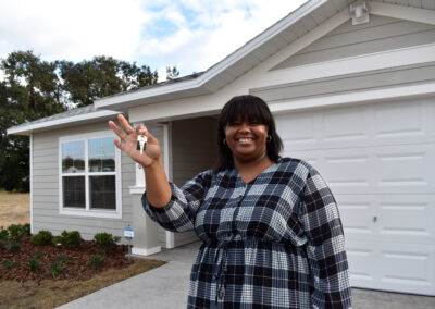 A smiling woman holds up her keys in front of her home.