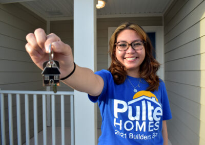 A smiling woman poses with house keys in front of her home.