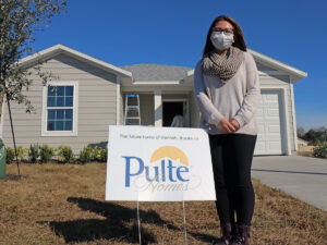 "A woman stands next to a sign that reads: ""The future home of Hannah thanks to Pulte Homes"""