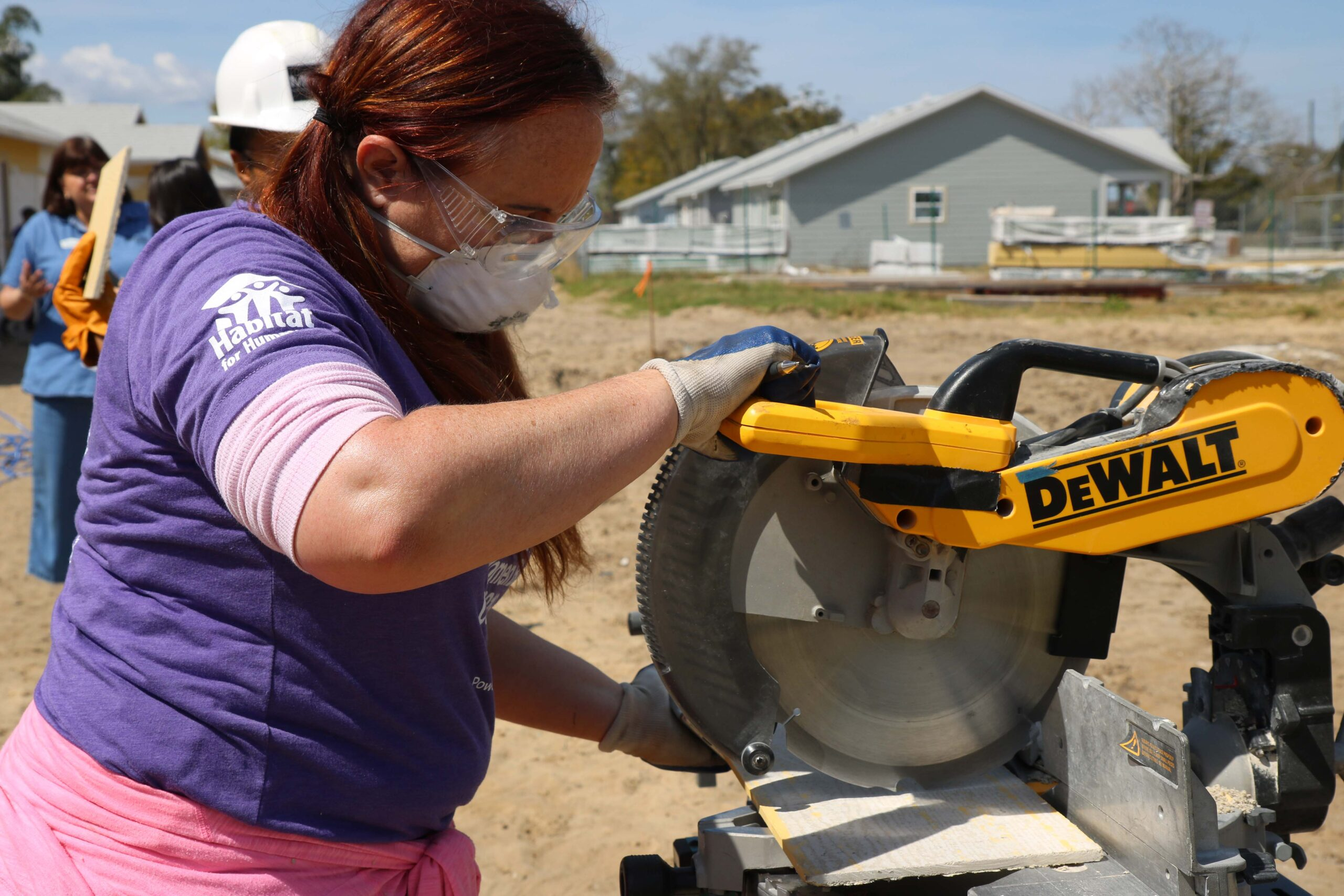 """Woman smiling and reaching up to paint siding of house with text overlay """"Women Build: A fundraising event"""" and Habitat Orlando & Osceola logo"""