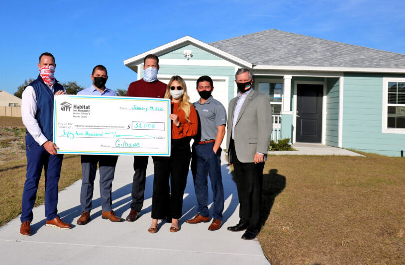 Six people stand in front of a house holding a large check.