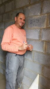 Volunteer coordinator David Bunzel poses next to a message he wrote on a concrete wall for a future Habitat homeowner